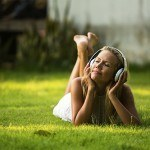 Woman laying the grass listening to music