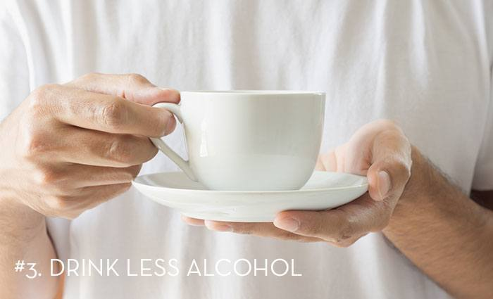 someone holding a mug and saucer with the words Drink Less Alcohol