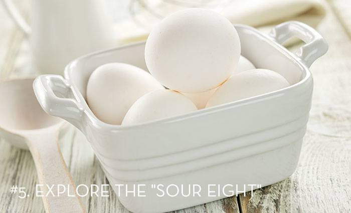 a white ceramic dish filled with eggs with the words Explore the Sour Eight