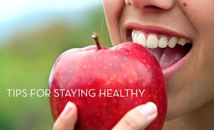 a woman eating an apple with words tips for staying healthy