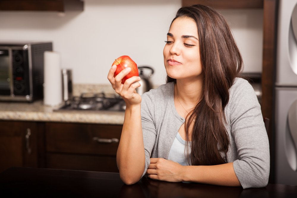 a person eating an apple in a kitchen