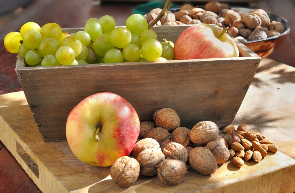a wooden box of apples grapes walnuts and almonds