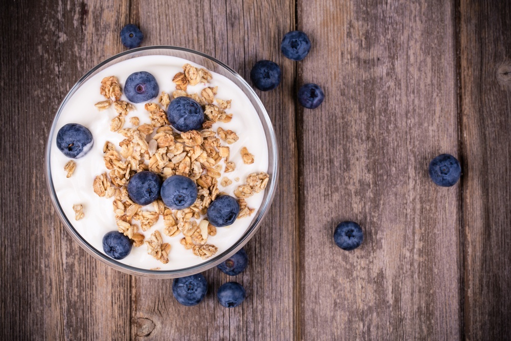 a bowl of yogurt granola and blueberries on a wooden table