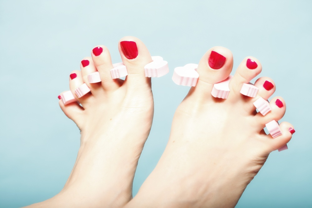 a pair of feet with fresh red nail polish and pedicure toe separators