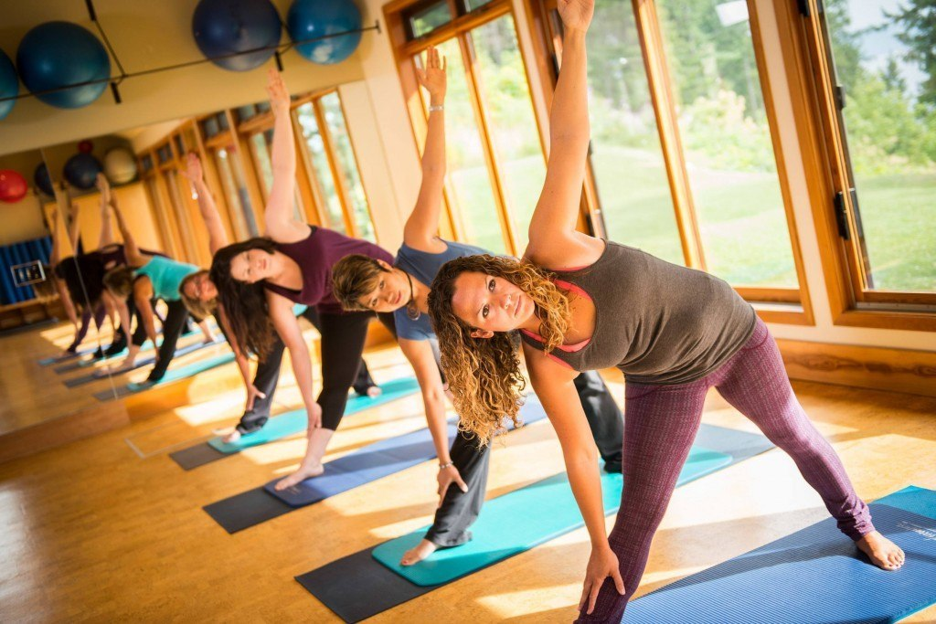 four people taking a yoga class at mountain trek