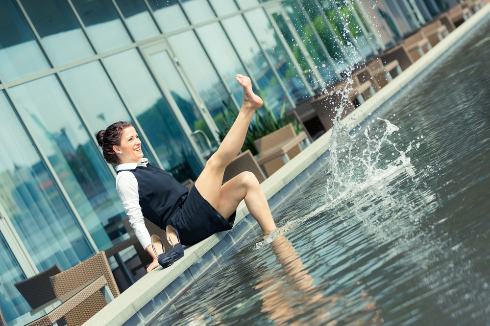 woman in a business suit without shoes playing in a fountain