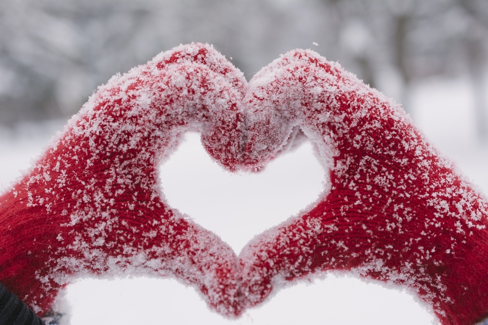 a pair of hands wearing red gloves making a heart shape in a winter scene