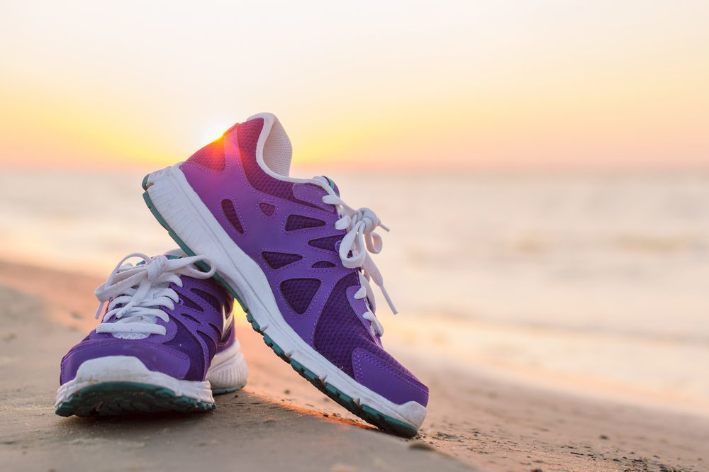 trainer shoes with a beach and sunset in the background