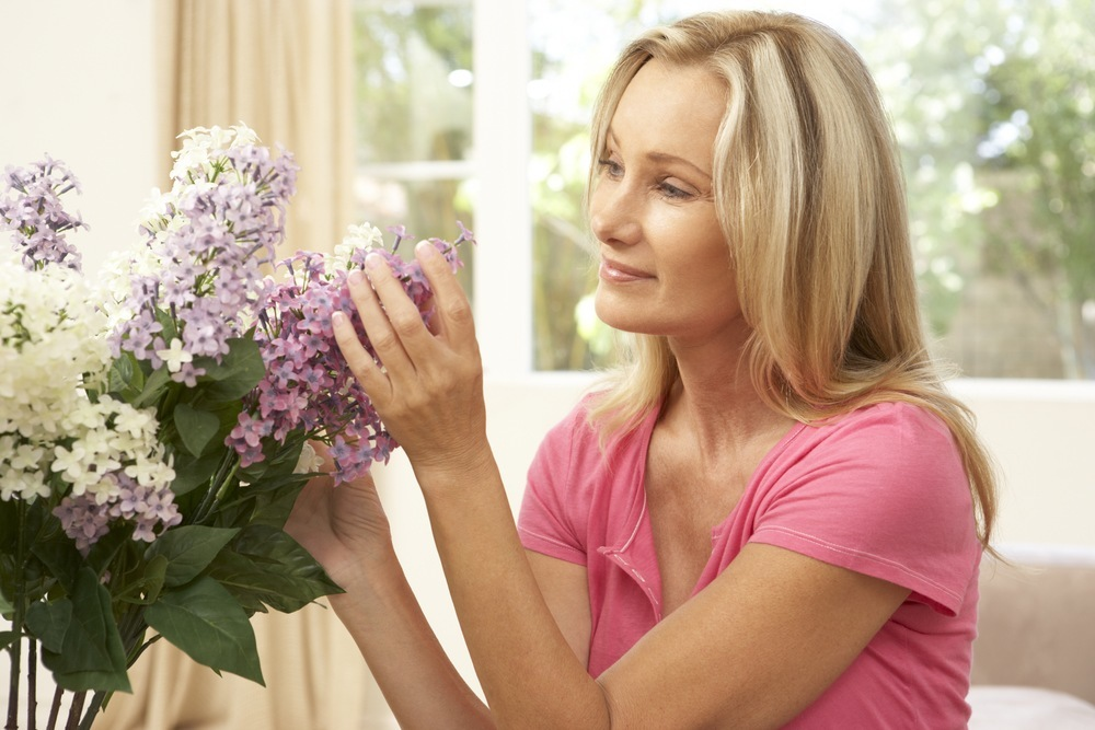 a woman smelling a bouquet of lilac flowers