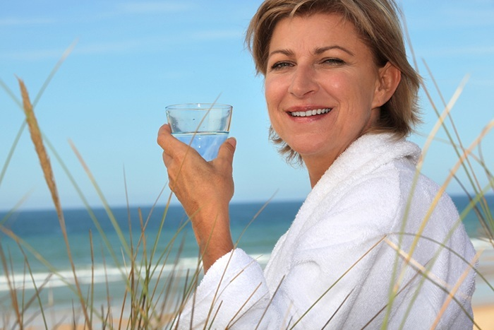 woman-on-the-beach-drinking-water-in-a-white-robe