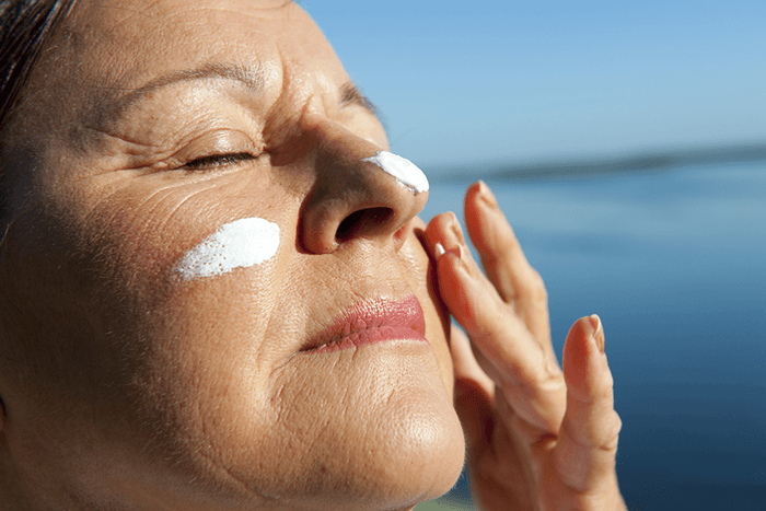 a person applying sunscreen to their face