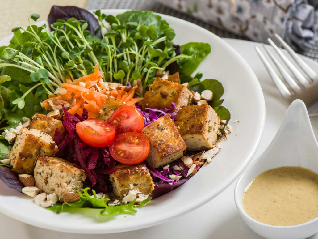 Colorful bowl of organic greens, baked tofu, fresh tomatoes, cabbage and grated carrots and garnished with crushed nuts.