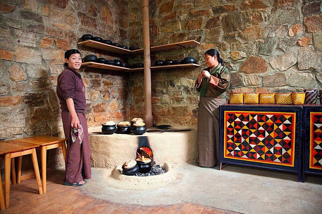 Two women standing in a traditional bhutanese kitchen