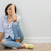 woman sitting on floor with hand on head