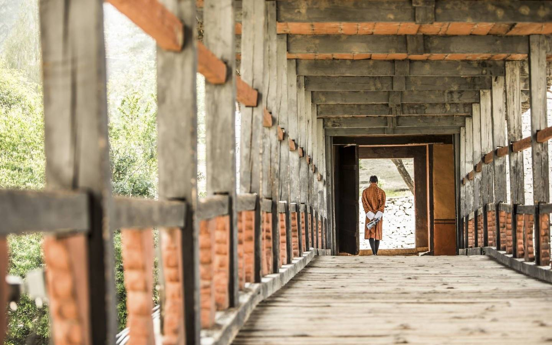 A Local bhutanese walks a traditional bridge Nyamai Zam. Seen on Mountain Trek Adventure Trek
