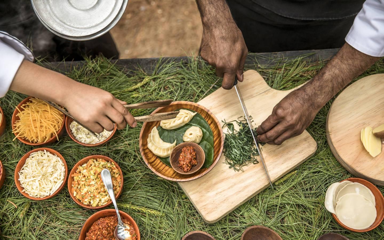 Man demonstrating Bhutanese cooking as experienced on Mountain Trek Adventure Trek