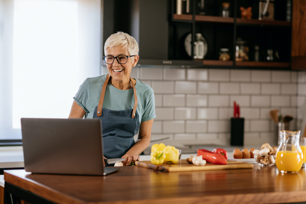 woman cooking in front of her laptop
