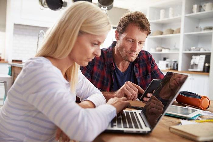 a couple in their kitchen both on their own tech devices