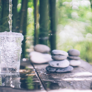 Clean water pouring into the glass next to the stones on the old wooden table