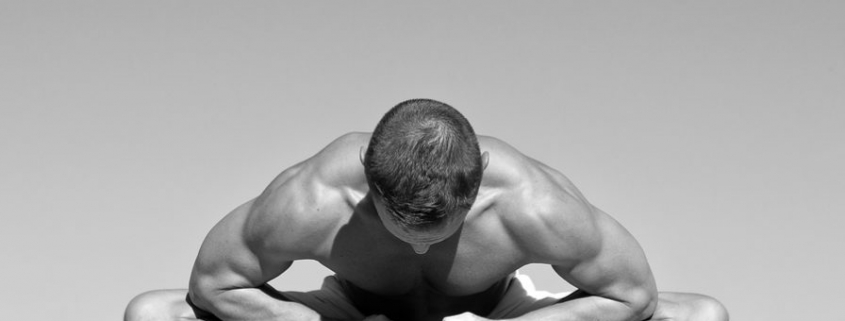 Strong Man Practicing Yoga bend over grabbing toes