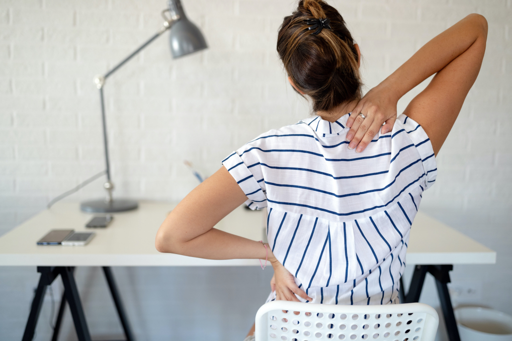 Overworked woman with back pain in office sitting on chair with bad posture