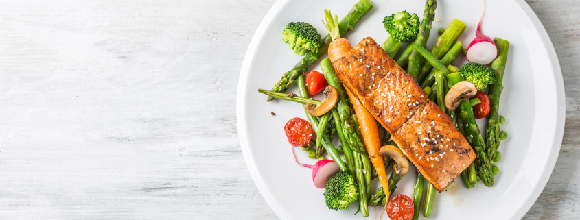 Plate with cooked salmon and veggies on blank table