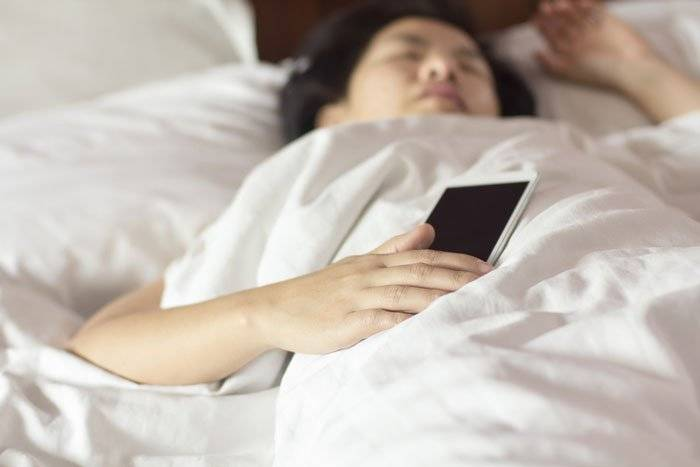 someone laying in bed sleeping and holding a cellphone