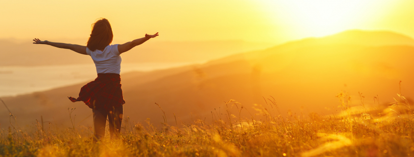 Happy woman standing with her back on the sunset in nature in summer with open hands