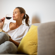 Pretty, young woman drinking some nice red wine at home, in the evening after work on her sofa (color toned image; shallow DOF)