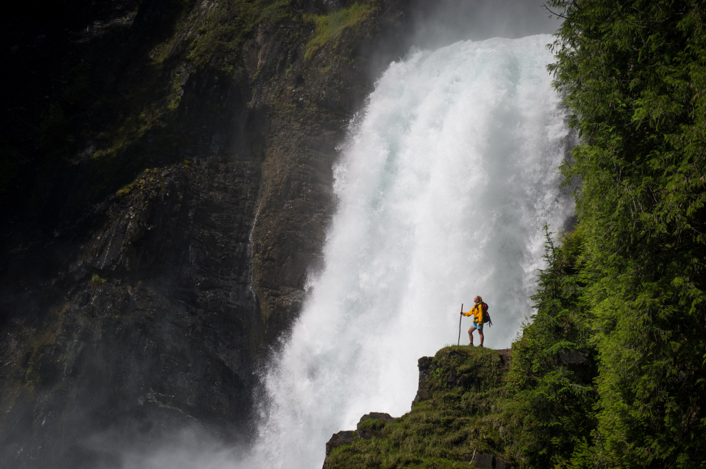 female hiker standing in front of waterfall