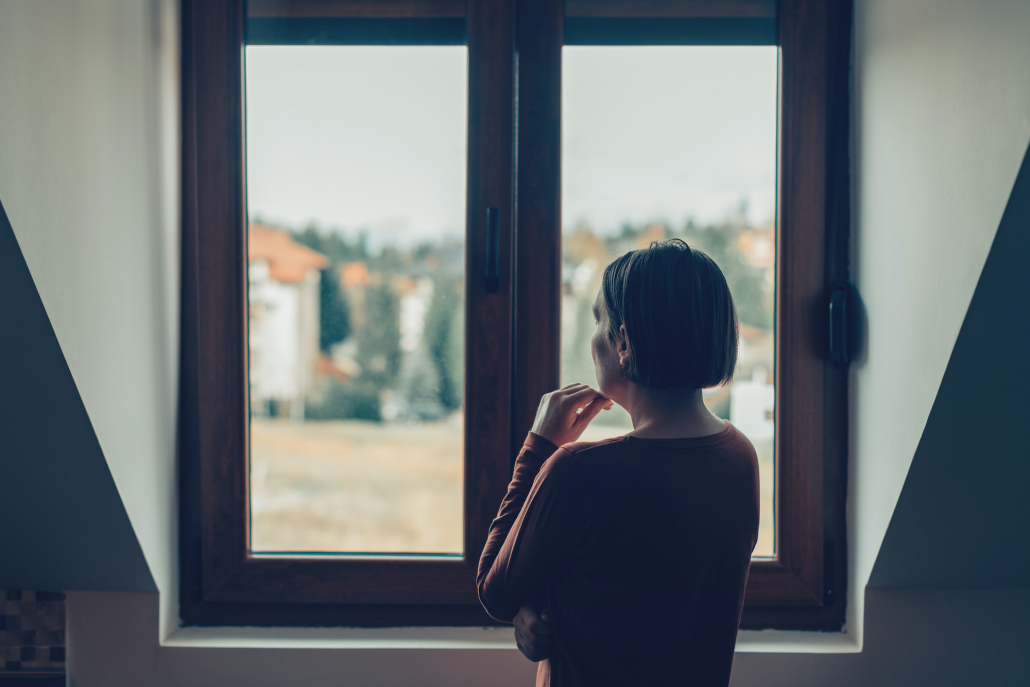 Sad woman looking out of the window in loft apartment