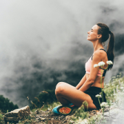 a woman sitting on a hiking trail meditating