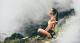 a woman sitting on a hiking trail meditating