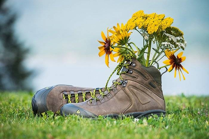hiking boots on grass with flowers