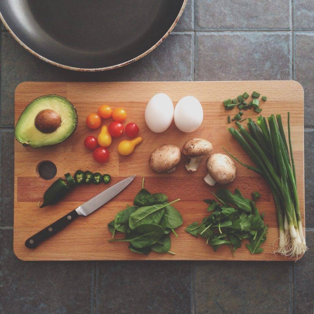 cutting board and knife with healthy nutritious vegetables and eggs