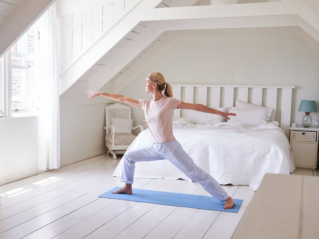 a woman doing morning yoga in her bedroom