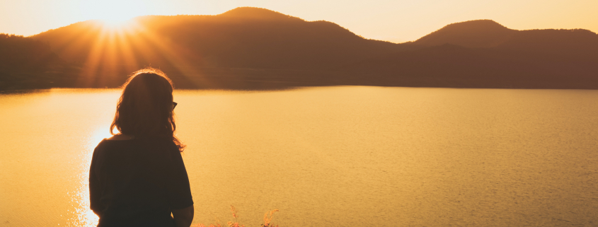 a woman Relaxing, sitting overlooking a lake and mountains